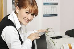 Woman in office smiling. Woman smiling At work in the office stock image