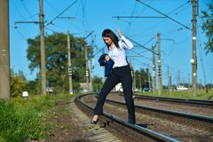 A woman in an office suit breaks the traffic rules and crosses the railway in a forbidden place during the day. Woman running on railway, run away, need to royalty free stock image