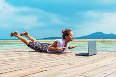 Woman in office suit doing yoga with laptop Stock Image