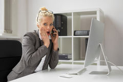 Woman in office talking on the phone and being shocked Stock Photo