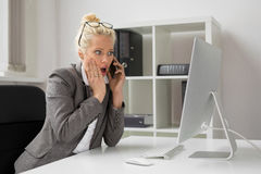Woman in office talking on the phone and being shocked Stock Images
