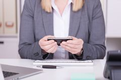 Woman at the office typing and messaging with her mobile phone stock image