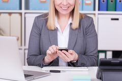 Woman at the office typing and messaging with her mobile phone royalty free stock photos