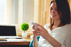 A woman in the office at work. Young business woman, laughing, writing SMS while sitting at the table. Multitasking concept. Telework concept. Work at home Royalty Free Stock Image