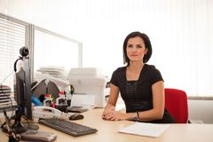 Woman office worker at desk. Young woman or female office worker sitting at a large office desk Stock Images