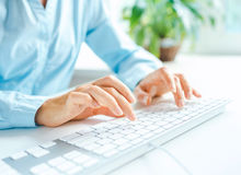 Woman office worker typing on the keyboard Stock Images