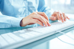Woman office worker typing on the keyboard Royalty Free Stock Photos