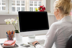 Woman in office working on stationary computer Stock Image