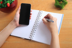 Woman office write notes and use smart phone on wooden table. Royalty Free Stock Photos