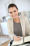 Woman in office writing on agenda Stock Photography
