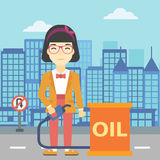 Woman with oil barrel and gas pump nozzle. An asian woman standing near oil barrel. Woman holding gas pump nozzle on a city background. Woman with gas pump and Stock Photography