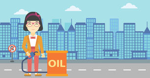 Woman with oil barrel and gas pump nozzle. An asian woman standing near oil barrel. Woman holding gas pump nozzle on a city background. Woman with gas pump and Royalty Free Stock Photo