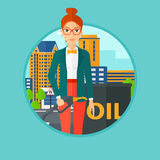Woman with oil barrel and gas pump nozzle. A woman standing near oil barrel. Woman holding gas pump nozzle on a city background. Woman with gas pump and oil Royalty Free Stock Images