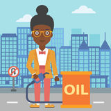 Woman with oil can and filling nozzle. An african-american woman standing beside the oil can and holding filling nozzle on a city background vector flat design Stock Photo