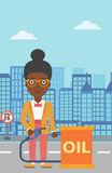 Woman with oil can and filling nozzle. An african-american woman standing beside the oil can and holding filling nozzle on a city background vector flat design Royalty Free Stock Images