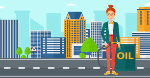 Woman with oil can and filling nozzle. A woman standing beside the oil can and holding filling nozzle on a city background vector flat design illustration Royalty Free Stock Photo