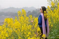 Woman and oilseed rape flower Stock Photos