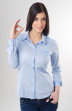 Woman with okay. Smiling woman with okay gesture on light background Royalty Free Stock Photo
