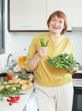 Woman with okra in domestic kitchen Stock Image