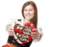 Woman in Oktoberfest dirndl holds heart royalty free stock photos