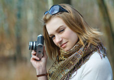 Woman with old camera. Beautiful young woman making photo using old camera royalty free stock photo