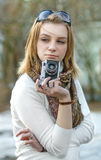 Woman with old camera. Beautiful young woman making photo using old camera stock photography