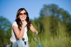 Woman with old-fashioned bike in meadow Stock Images