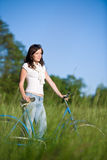 Woman with old-fashioned bike in meadow Royalty Free Stock Image