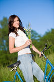 Woman with old-fashioned bike and summer flower Stock Image