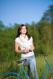 Woman with old-fashioned bike in summer meadow Stock Images
