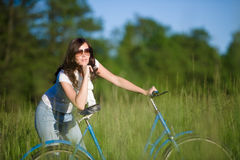 Woman with old-fashioned bike in summer meadow Stock Photos