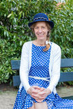 Woman in old-fashioned clothes sitting on bench in park. Dutch woman dressed in blue old-fashioned clothes sitting on bench in park. The caucasian woman is royalty free stock image