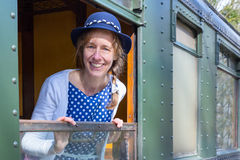 Woman in old-fashioned clothes in window of steam train Stock Photo