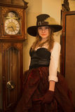 Woman at old fashioned dress near clock Royalty Free Stock Image