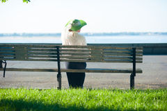 Woman in old-fashioned dress sitting on the bench Stock Photography