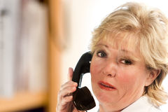 Woman on old fashioned phone. Answering the phones the old fashioned way stock image