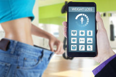 Woman with old jeans and weight loss apps. Close up of woman wearing her old jeans at fitness center with weight loss applications on the smartphone screen Stock Photos