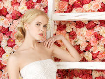 Woman with old ladder and background full of roses Stock Image