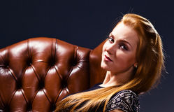 Woman in old leather armchair Stock Images