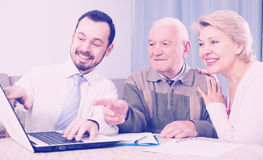 Woman and old man consider contract Royalty Free Stock Image