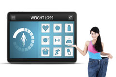 Woman with old pants shows weight loss app Royalty Free Stock Photo
