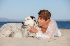 Woman with old pet mongrel dog. On beach Royalty Free Stock Photo