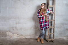 Woman in the old room. Young woman in checkered shirt standing in the old room with ladder on the gray textured wall background Stock Photo