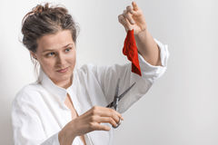 Woman  with old scissors and a small piece of red cloth. In a white background Stock Photos