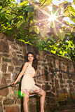 Woman by old stone wall at sunny day Stock Photography