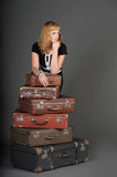 Woman and old suitcases. Young woman and a lot of old suitcases Royalty Free Stock Photos