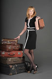 Woman and old suitcases. Young woman and a lot of old suitcases Stock Photography