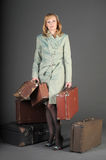 Woman and old suitcases. Young woman and a lot of old suitcases Stock Photo