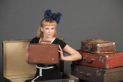 Woman and old suitcases. Young woman and a lot of old suitcases Royalty Free Stock Photography
