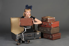 Woman and old suitcases. Young woman and a lot of old suitcases Royalty Free Stock Images